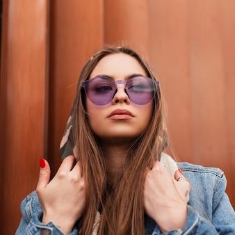 Modieuze portret amerikaanse jonge vrouw in een stijlvol blauw spijkerjasje in trendy glamoureuze paarse bril in de buurt van een metalen moderne muur in de rij. stedelijk mooi meisjesmodel. straatmode. detailopname.