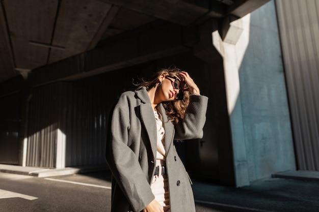 Modieuze portret van een mooi meisje met zonnebril in een vintage jas met een trui rechtzetten haar krullend haar in de stad. stedelijke casual vrouwelijke stijl en schoonheid