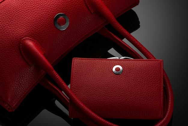 Modieuze rode damestas en portemonnee op een donkere achtergrond