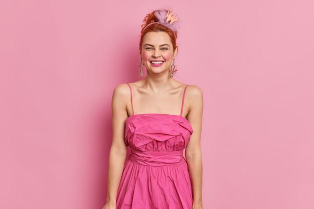 Modieuze roodharige jonge vrouw gekleed in jaren negentig stijl draagt roze jurk glimlacht positief heeft lichte make-up vormt indoor bereidt zich voor op datum of speciale gelegenheid. mode en vintage concept Gratis Foto