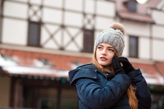Modieuze roodharige jonge vrouw in trendy outfit poseren op straat in kiev