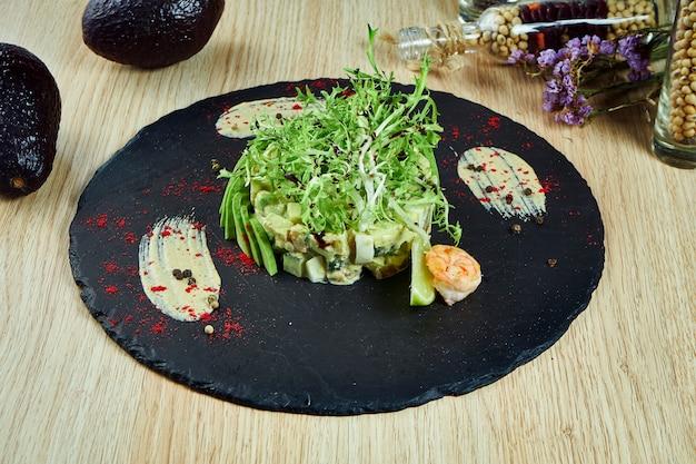 Modieuze russische salade olivier met avocado en garnalen op een zwarte leisteen schoolbord. sluit omhoog mening over tasque zeevruchtensalade
