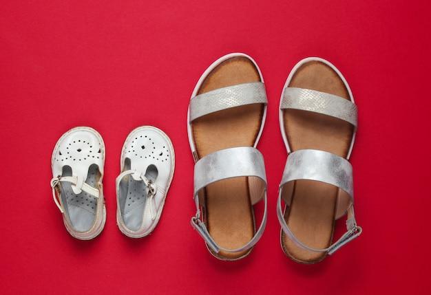Modieuze sandalen voor kinderen en volwassenen op rood.