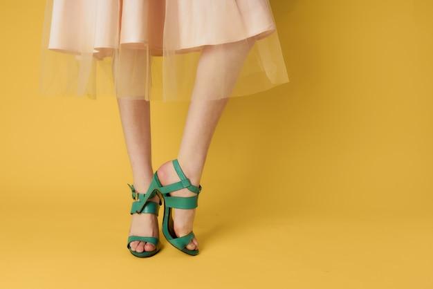 Modieuze schoenen groene schoenen vrouwelijke voeten winkelen gele achtergrond