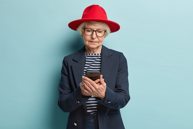 Modieuze senior vrouw sms't op smartphone, tevreden met tarieven op internet, winkelt online, kiest nieuwe outfit in webwinkel, draagt stijlvolle rode hoofddeksels, bril en formeel jasje