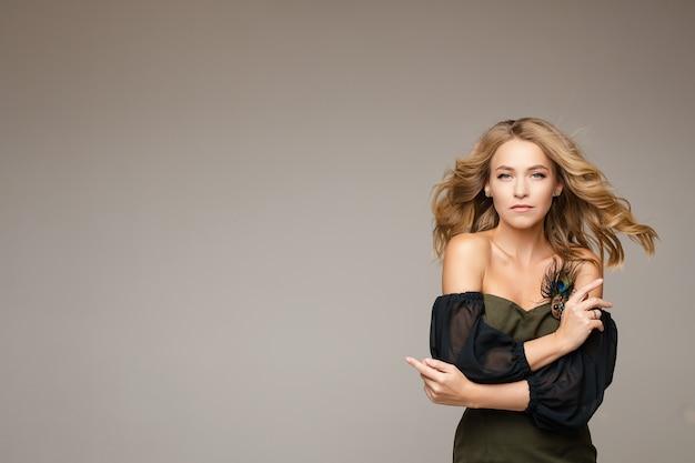 Modieuze sensuele vrouw met lang golvend blond haar in stijlvolle jurk met blote schouders en broche op borst camera kijken met omhelzen zichzelf gebaar. kopieer ruimte.