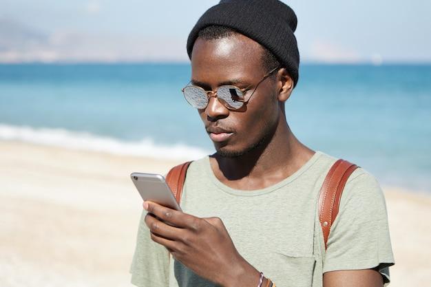 Modieuze serieuze afrikaanse man-backpacker die foto's plaatst via sociale media, met behulp van een 3g- of 4g-internetverbinding op een mobiele telefoon terwijl hij de wereld rondreist, blauwe oceaan en lucht in de horizon