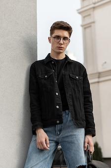 Modieuze serieuze jonge man mannequin in stijlvolle jeans jeugd vrijetijdskleding in vintage bril met rugzak rusten in de buurt van muur in de stad. stedelijke trendy man buitenshuis. lentecollectie herenkleding