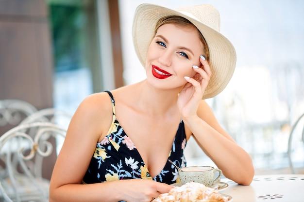Modieuze sexy mooie jonge aantrekkelijk meisje zit in een café op het terras in de stad in een mooie avondjurk en hoed drinkt koffie en eet een taart