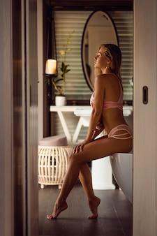 Modieuze slanke mooie jonge vrouw zich klaar in huis badkamer. sportief vrouwelijk figuur in roze lingerie, ijdelheid levensstijl.
