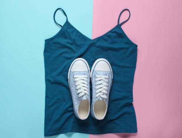 Modieuze sneakers liggen op t-shirt op blauw roze pastel, bovenaanzicht