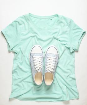 Modieuze sneakers liggen op t-shirt op wit, bovenaanzicht