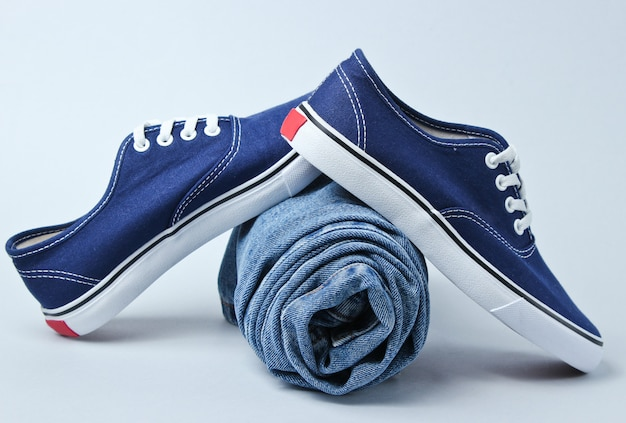 Modieuze sneakers met opgerolde jeans op een grijze tafel.