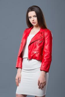 Modieuze stijl, mode dameskleding, kleurencombinatie. mooi donkerbruin meisje in witte kleding en rood leerjasje geïsoleerde grijze achtergrond.