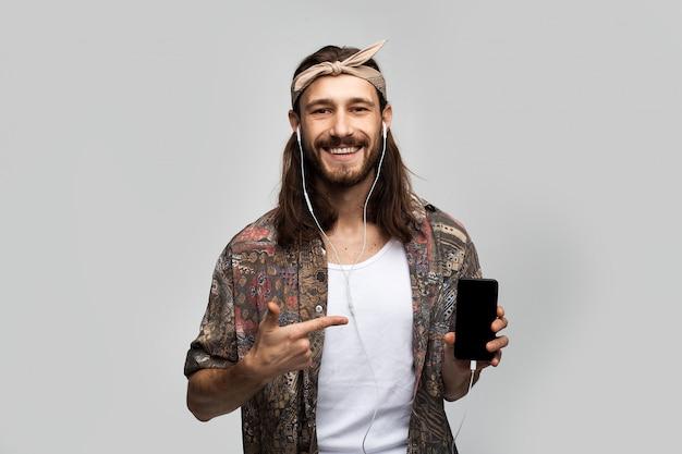 Modieuze stijlvolle hipster-man luistert naar muziek met behulp van een mobiele applicatie online, in een koptelefoon op een witte achtergrond geeft de plaats aan voor plaatsing op het smartphonescherm