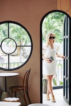 Modieuze stijlvolle jonge blonde vrouw in zonnebril café deur invoeren