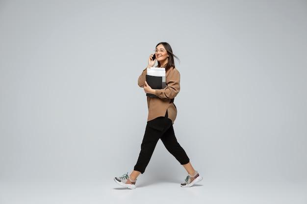 Modieuze stijlvolle jonge vrouw in vrijetijdskleding op grijze achtergrond bodypositive character