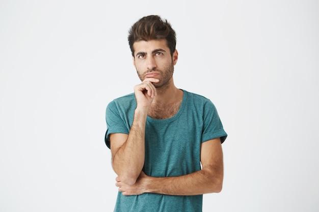 Modieuze, stijlvolle man met donkere ogen in casual kleding die opzij kijkt met een rustige en doordachte uitstraling. nadenkend man met verbaasde uitdrukking na te denken over iets of bouwplannen