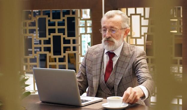 Modieuze, stijlvolle oude man, gepensioneerde, grijsharige man met een baard zittend aan een tafel en bezig met een laptop in een kantoor, restaurant, café