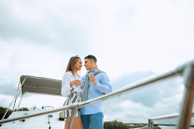 Modieuze stijlvolle staande jonge paar poseren op luxe motorboot jacht op blauwe hemel met wolken en zee landschapsmuur bij daglicht uitzicht vanaf het water