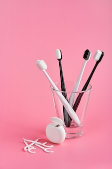Modieuze tandenborstel met zachte haren. populaire tandenborstels. hygiënetrends. kit voor mondhygiëne. tandenborstels in glas, flosdraad en tandenstokers op een roze ondergrond.