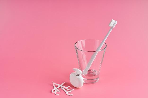 Modieuze tandenborstel met zachte haren. populaire tandenborstels. hygiënetrends. kit voor mondhygiëne. tandenborstels in glas, flossdraad en tandenstokers op een roze achtergrond.