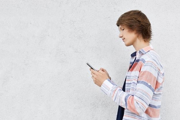 Modieuze tiener die zich zijdelings houdend celtelefoon bevinden die over witte concrete muur met exemplaarruimte wordt geïsoleerd