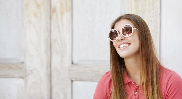 Modieuze tienermeisje met charmante glimlach binnenshuis ontspannen, stijlvolle ronde zonnebril dragen. aantrekkelijke glimlachende jonge vrouw gekleed in poloshirt thuis. mensen