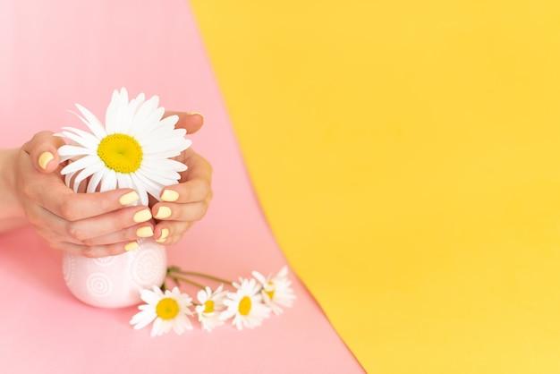 Modieuze trendy vrouwelijke manicure, de handen van de mooie jonge vrouw op roze en blauwe achtergrond.
