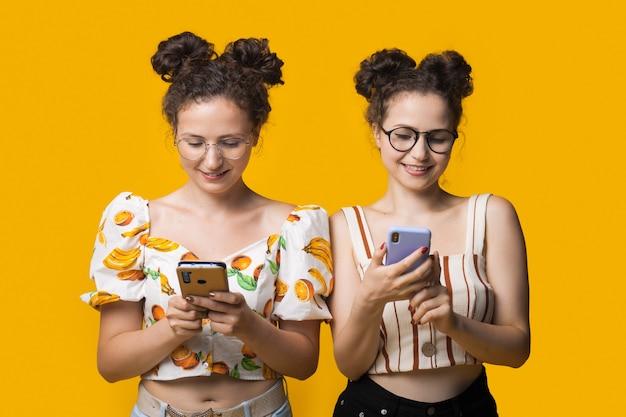 Modieuze tweeling met krullend haar en bril chatten op mobiel
