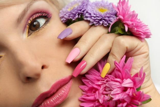 Modieuze veelkleurige make-up en manicure op lange nagels van een meisje met asters.