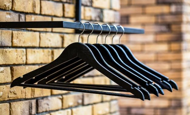 Modieuze verschillende soorten hangers. houten hangers jas. veel houten zwarte hangers aan een stang. winkelconcept, verkoop, ontwerp, lege hangers. houten kleerhanger kleding.