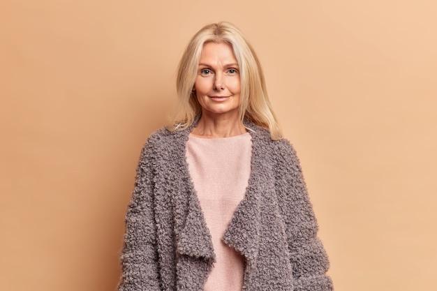 Modieuze vijftigjarige vrouw met blond haar gekleed in trui en warme jas kijkt direct naar voren met serieuze uitdrukking vormt tegen beige muur blijft mooi in elke leeftijd