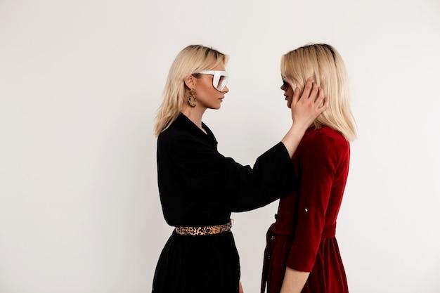 Modieuze vriendinnen in stijlvolle jurken met trendy bril kijken elkaar aan en strijken hun haar binnenshuis