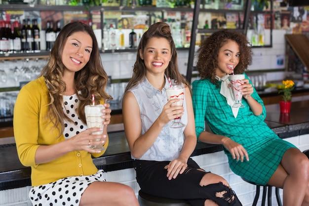 Modieuze vriendinnen met drankje in restaurant