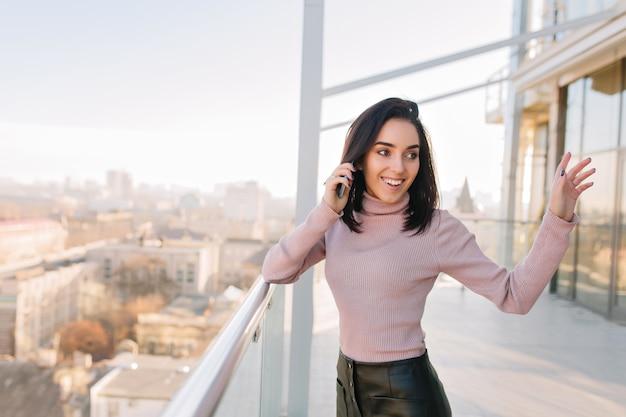 Modieuze vrolijke brunette jonge vrouw met plezier op terras met uitzicht op de stad. praten aan de telefoon, echte positieve gezichtsemoties uiten, geluk, opgewonden, ontspannen.