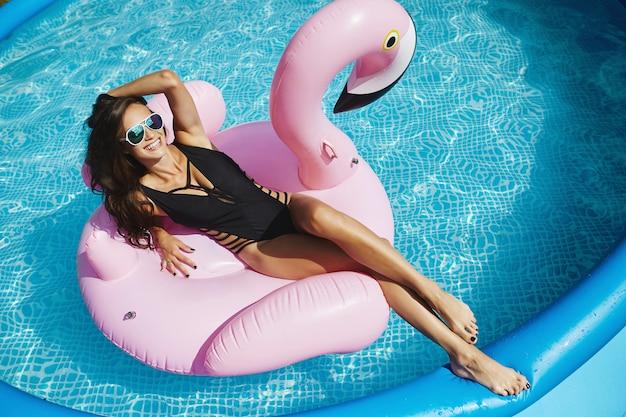 Modieuze, vrolijke en lachende brunette model vrouw met perfect sexy lichaam in stijlvolle zwarte bikini en glamoureuze zonnebril, poseren op een opblaasbare roze flamingo bij het zwembad buiten