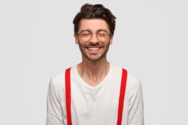 Modieuze vrolijke man hipster met brede glimlach, sluit ogen van gelach