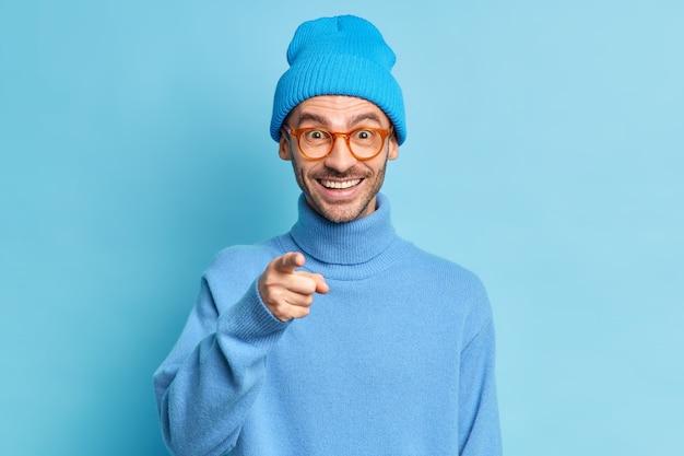 Modieuze, vrolijke man met borstelharen direct in de camera voelt zich blij