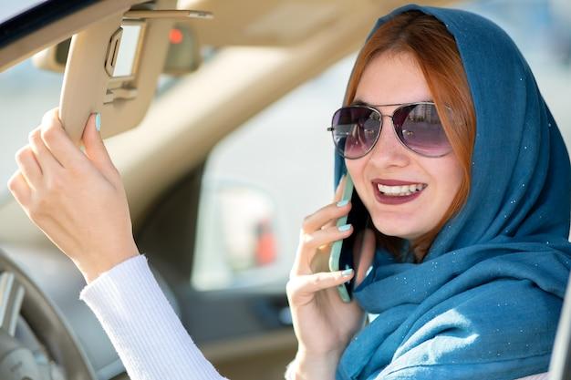 Modieuze vrouw bestuurder in sjaal en zonnebril praten op mobiele telefoon tijdens het besturen van een auto.