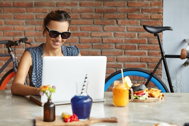 Modieuze vrouw blogger schrijven van nieuwe post op laptopcomputer, met behulp van high-speed internetverbinding tijdens de lunch