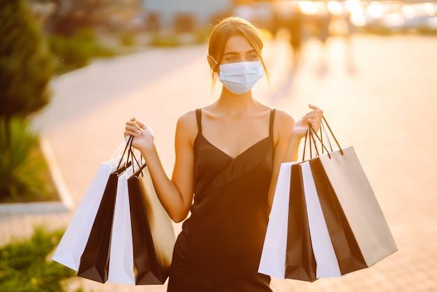 Modieuze vrouw die beschermend medisch masker met boodschappentassen draagt bij zonsondergang.