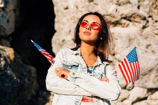 Modieuze vrouw die de weinig vlaggen van de vs op rotsen houdt