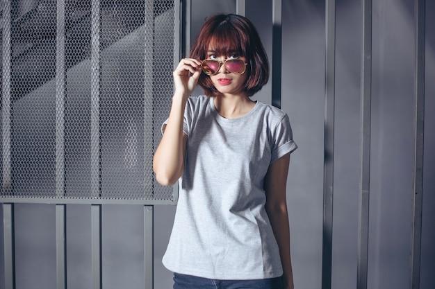 Modieuze vrouw die grijze t-shirt en zonnebril draagt