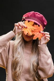 Modieuze vrouw die haar gezicht achter droge esdoornbladeren verbergt tegen zwarte achtergrond