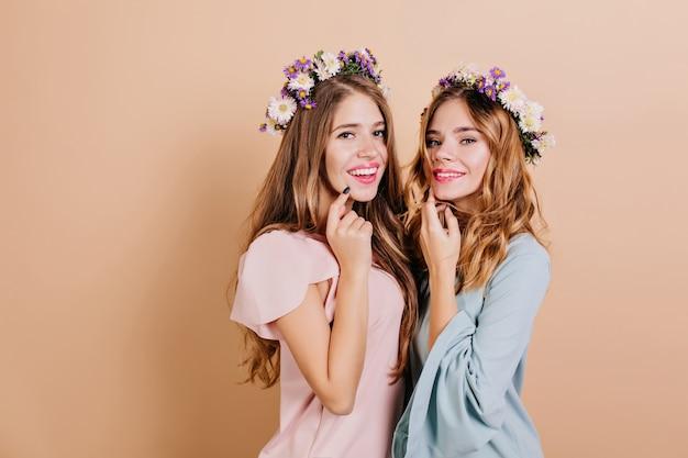 Modieuze vrouw die in bloemkroon geluk uitdrukt tijdens fotoshoot met zus