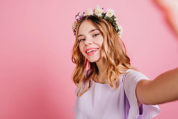 Modieuze vrouw die in bloemkroon selfie met zacht glimlach maakt