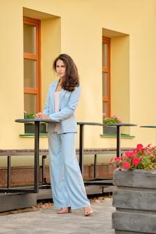 Modieuze vrouw die in hemelsblauw pantsuit dichtbij de lijst bij koffieterras wachten
