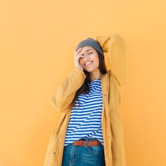 Modieuze vrouw die jasje op gestreepte t-shirt draagt die terwijl het bekijken camera stelt