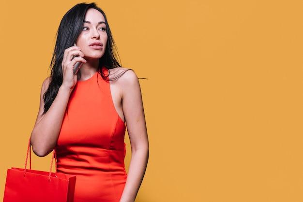 Modieuze vrouw die met het winkelen zak op telefoon spreekt